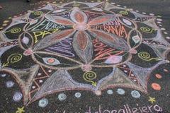 Молодые люди рисуя мандалу для любов и мира в улицах Каракаса во время светомаскировки Венесуэлы стоковое изображение