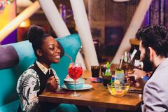 Молодые люди сидя в кафе и говорить Встреча молодого человека и женщины на таблице кафа стоковая фотография rf