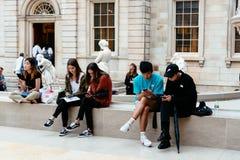 Молодые люди сидя на музее с мобильными телефонами стоковое фото rf