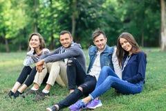 Молодые люди сидя на траве в природе, смотря камеру Стоковые Фото