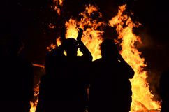 Молодые люди силуэтов вокруг костра огня пламен реветь Стоковое Изображение RF