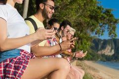Молодые люди собирает используя друзей пальм парка умных телефонов клетки тропические беседуя онлайн летние каникулы моря праздни Стоковая Фотография RF