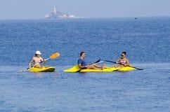 Молодые люди сплавляться на море в красивой природе с островом на предпосылке Стоковые Фото