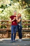 Молодые люди с вкусной едой outdoors в парке Счастливые друзья на пикнике Стоковая Фотография RF