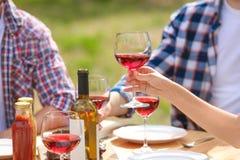 Молодые люди с стеклами вина на таблице outdoors Стоковое Фото