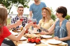 Молодые люди с стеклами вина на таблице outdoors Стоковые Фотографии RF
