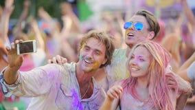 Молодые люди усмехаясь и представляя для selfie на smartphone на фестивале цвета акции видеоматериалы