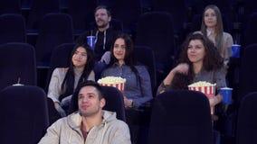 Молодые люди фильма вахты на кинотеатре стоковое изображение rf