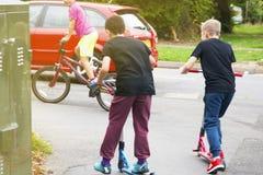 Молодые мальчики ехать счастливо на самокате, сфотографированном от позади Праздники, летние каникулы стоковое фото rf