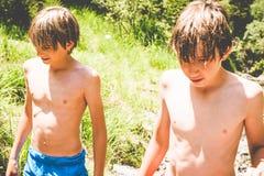 Молодые мальчики имеют потеху на малом реке стоковая фотография