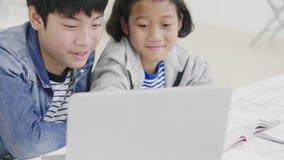 Молодые мальчики используют компьютеры для того чтобы научить и объяснить домашней работе К друзьям с выражениями лица и счастлив сток-видео