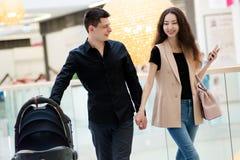 Молодые мама и папа идут ходить по магазинам для младенца Стоковая Фотография