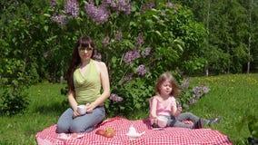 Молодые мать и дочь litlle на весне участвовать рядом с blossoming сиренью акции видеоматериалы