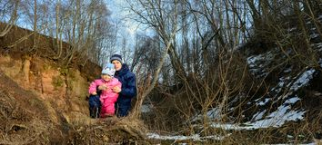 Молодые мать и маленькая девочка в солнце освещают внутри леса стоковое фото rf