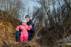 Молодые мать и маленькая девочка в солнце освещают внутри леса стоковые фотографии rf
