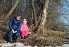 Молодые мать и маленькая девочка в солнце освещают внутри леса стоковое изображение rf