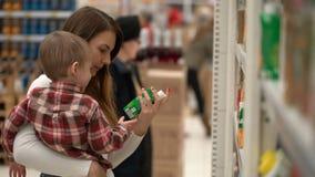 Молодые мать и сын покупают воду или сок в магазине видеоматериал