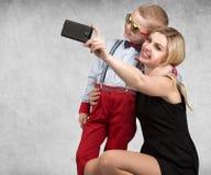 Молодые мать и сын сфотографированы на мобильном телефоне, делая selfie Стильный, ультрамодный, современный стоковая фотография rf