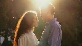 Молодые милые пары тратя интимное время совместно на парке осени Свет захода солнца, пирофакелы солнца Любовники наслаждаясь на д акции видеоматериалы