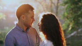 Молодые милые пары тратя интимное время совместно на парке осени Свет захода солнца, пирофакелы солнца Любовники наслаждаясь на д видеоматериал
