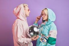 Молодые модные пары танцоров представляя с шариком диско на фиолетовой предпосылке стоковая фотография