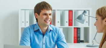 Молодые мужские и женские деловые партнеры обсуждая контракт Дело, офис, закон и законная концепция Стоковые Изображения