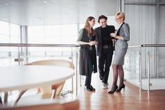 Молодые мужские и женские сотрудники обсуждая и планируя процесс производительной деятельности в офисе, усмехаясь студентах стоковое изображение