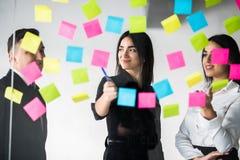 Молодые мужские и женские сотрудники писать остальные примечания для коллег планируя процесс производительной деятельности в офис стоковые фото