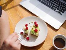 Молодые мужские руки и вкусное пирожное с чашкой поленик cofe с молоком и таблеткой на деревянном столе Бизнес Стоковое фото RF