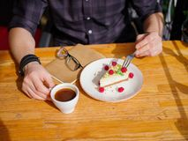 Молодые мужские руки и вкусное пирожное с чашкой поленик cofe с молоком и таблеткой на деревянном столе Бизнес Стоковое Изображение