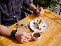 Молодые мужские руки и вкусное пирожное с чашкой поленик cofe с молоком и таблеткой на деревянном столе Бизнес Стоковая Фотография