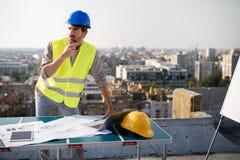 Молодые мужские светокопии инженера специалисту по конструкции рассматривая на строительной площадке стоковые изображения rf