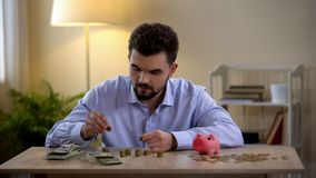 Молодые мужские считая монетки, копилка готовя, финансовая грамотность, бюджет стоковое изображение rf