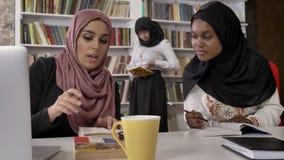 Молодые мусульманские женщины в hijab объясняя что-то к чернокожим женщинам в hijab, изучая в библиотеке и подготавливая для экза акции видеоматериалы