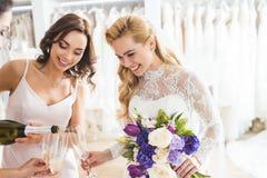 Молодые невесты держа стекла и бутылку шампанского в свадьбе Стоковая Фотография
