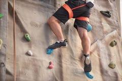 Молодые ноги альпиниста спортсмена взбираясь крытая стена взбираются Стоковая Фотография RF