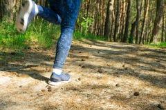 Молодые ноги бегуна женщины фитнеса бежать на лесе утра тропическом отстают стоковое изображение