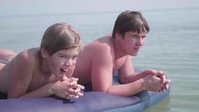Молодые отец и сын купают в море на раздувном тюфяке взволнованности положительные лето дня горячее видеоматериал