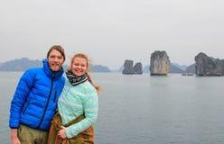 Молодые парень и девушка пар в sportswear обнимая и смеясь счастливо на фоне скал залива Ha длинного во время th стоковое изображение