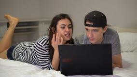 Молодые парень и девушка пар лежат перед компьтер-книжкой и говорят акции видеоматериалы