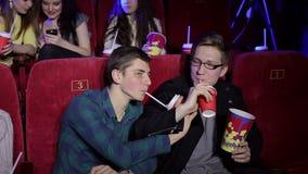 Молодые парни ослабляют в кино с попкорном и напитками видеоматериал