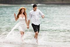 Молодые пары бежать вдоль воды на пляже стоковые фотографии rf