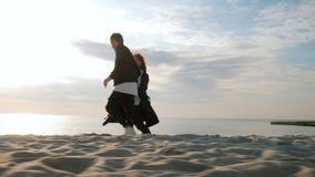 Молодые пары бежать на песчаном пляже Спарите иметь потеху, околпачивающ, держащ руки, наслаждаясь моментом Романтичный заход сол акции видеоматериалы