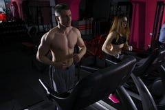 Молодые пары бежать на третбане в спортзале Стоковое Изображение RF