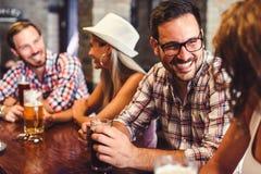 Молодые пары выпивая пиво и смеясь над совместно на баре стоковые фото
