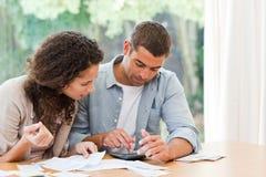 Молодые пары высчитывая их отечественные векселя Стоковое Фото