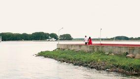 Молодые пары в влюбленности идя вдоль прогулки голубым морем акции видеоматериалы