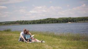 Молодые пары в влюбленности на дате на траве рекой Парень и девушка на прогулке с собакой видеоматериал