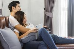 Молодые пары в влюбленности сидя на коричневой софе и наблюдая televi Стоковые Фото