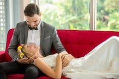 молодые пары в женихе и невеста свадьбы любов лежа вниз на красной софе совместно смотря один другого Новобрачные женщина портрет стоковое фото